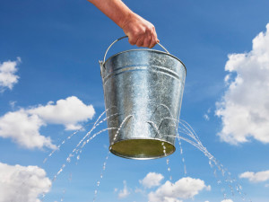 Man Holding Leaking Bucket --- Image by © Paul Hardy/Corbis